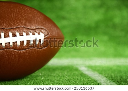 American football on green grass, close-up - stock photo