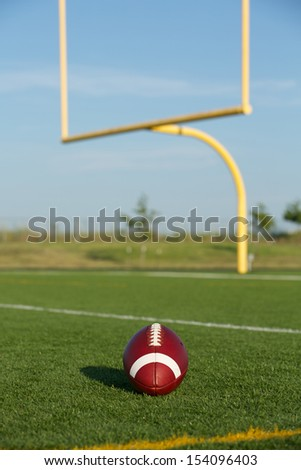 American Football on the Field with Goalposts or Uprights Beyond - stock photo