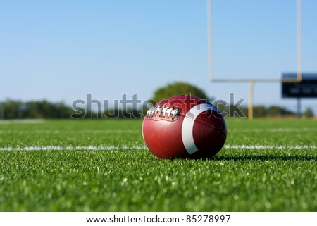 American Football on the Field with the Goal Posts beyond - stock photo