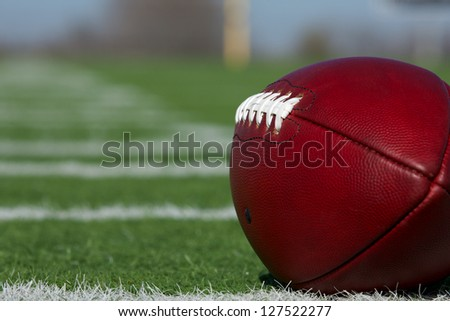 American Football on the Field with the hashmark yardlines carrying off - stock photo