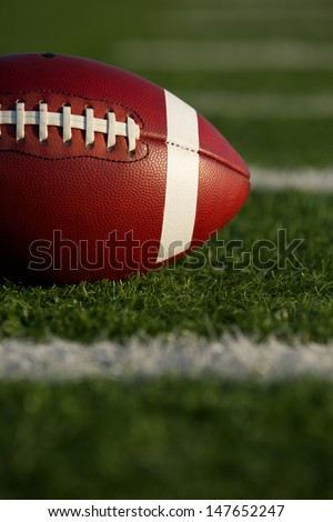 American Football on the Field with Yard Lines Beyond and room for copy - stock photo