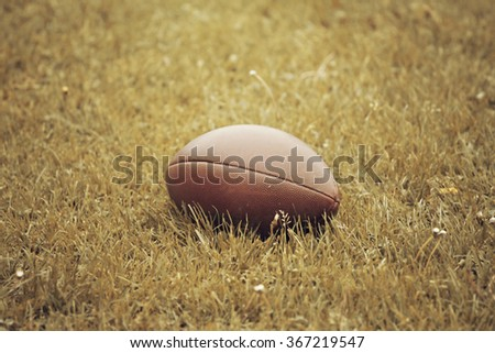 American Football on the ground - retro styled photo - stock photo