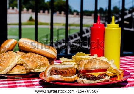 American football party with cheeseburger, hot dog, potato chips, ketchup and mustard bottles and buns.  Football field in background. - stock photo