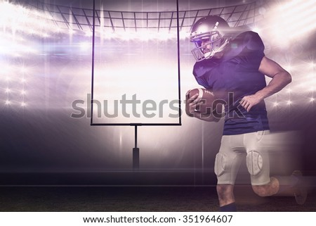 American football player holding ball in mid-air against american football arena - stock photo