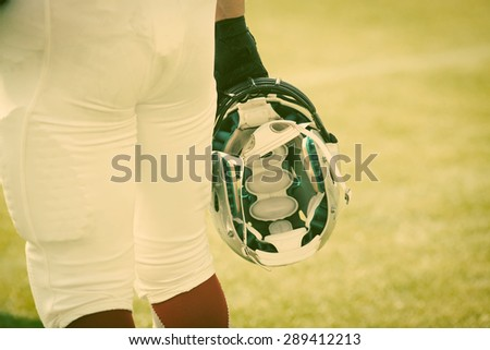 american football player holding his  helmet - sport concept - stock photo