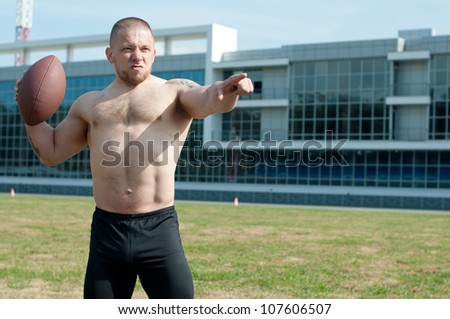 American football player holding the ball and making a pointing gesture - stock photo