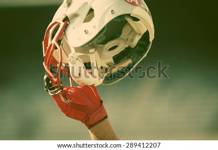 american football player holding up his  helmet - victory concept - stock photo