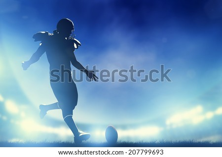 American football player kicking the ball, kickoff. Night stadium lights - stock photo