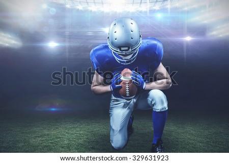 American football player kneeling against american football arena - stock photo