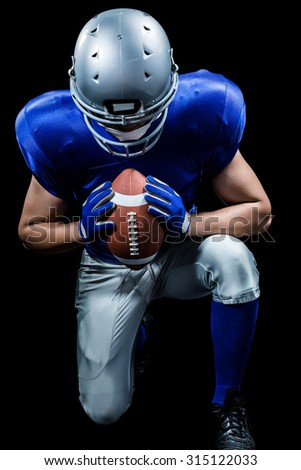 American football player kneeling while holding ball against black background - stock photo