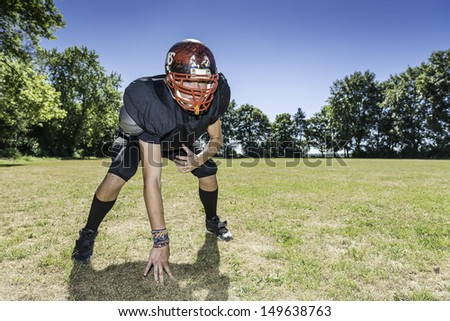 American football player offensive Lineman in in action at three point stance - stock photo