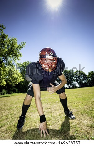 American football player offensive Lineman in three point stance - stock photo