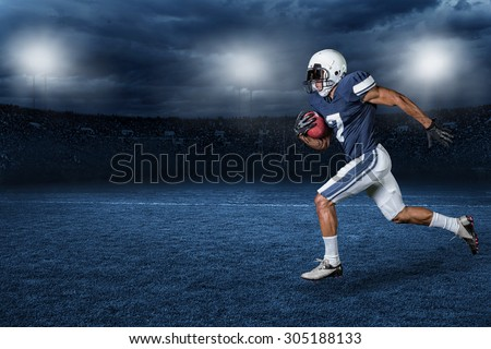 American Football Player Running for a touchdown in a large outdoor professional football stadium at night - stock photo