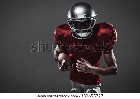 American football player running with ball against grey - stock photo