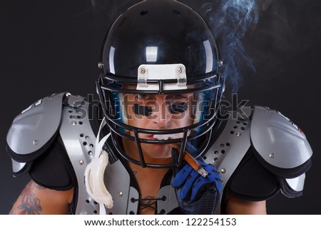 American football player smoking cigar portrait over a dark background - stock photo