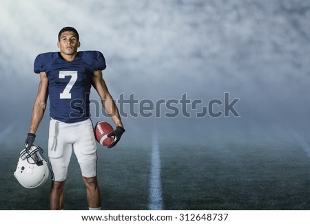 American Football player standing in a stadium at night ready to play and win - stock photo