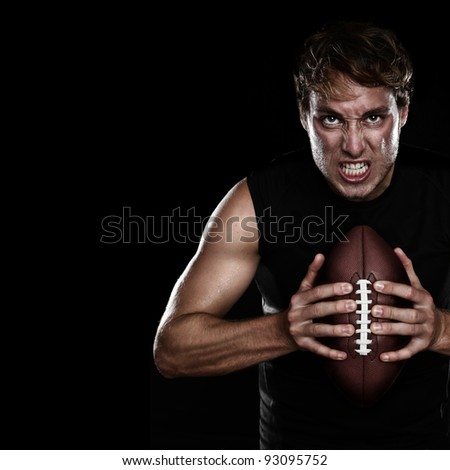 American football player staring aggressive holding american football on black background. Strong fit Caucasian fitness man with black copy space. - stock photo