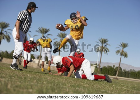 American football player trying to block rivalry team member while referee watching on field - stock photo