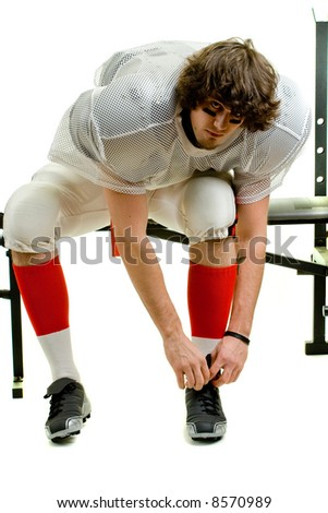 American football player. Tying shoe on weight bench. - stock photo