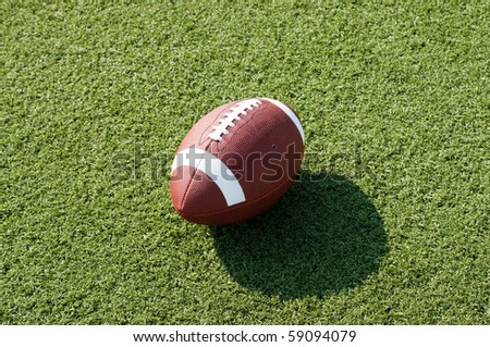 American football sitting on field with afternoon shadow showing. - stock photo