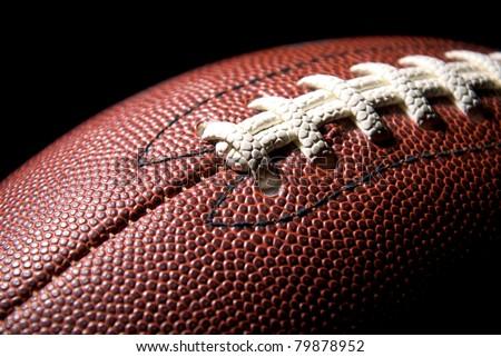 American football, studio shot, black background - stock photo