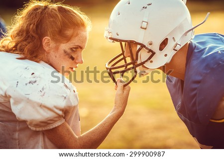 American football woman player in action on the stadium. little girl playing with big men in football on the field at sunset - stock photo