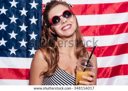 American girl. Cheerful young woman holding a cup of juice and wearing sunglasses while standing against American national flag - stock photo