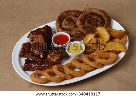American grilled ribs on the grill topped with barbecue sauce with onion rings and hot crispy potatoes - sausages hot roasted, chicken wings in teriyaki sauce, American food - fast food - stock photo