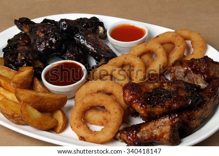 American grilled ribs on the grill topped with barbecue sauce with onion rings and hot crispy potatoes - , chicken wings in teriyaki sauce, American food - fast food - stock photo