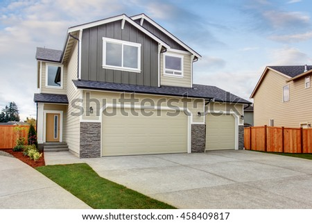 American house exterior with two garage spaces and concrete floor driveway. - stock photo