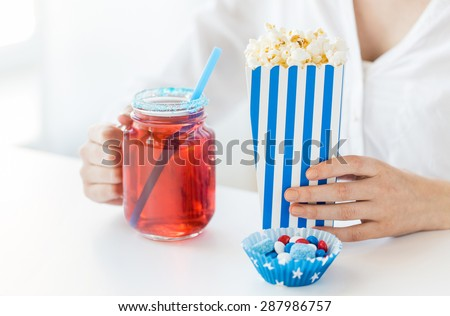 american independence day, celebration, patriotism and holidays concept - close up of woman eating popcorn with drink in glass mason jar and candies at 4th july party - stock photo