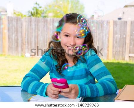 American latin teen girl with smartphone doing homework on backyard - stock photo