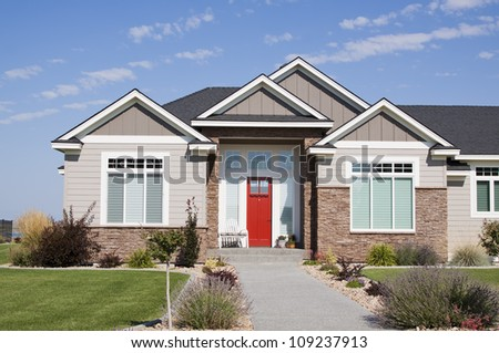 american luxury suburban house with landscaping on a front and blue sky - stock photo