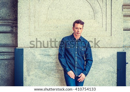 American Man Street Casual Fashion in New York. Wearing Denim shirt, jeans, a middle 30 years old guy standing against vintage style wall on street, looking at you. Instagram filtered effect.  - stock photo