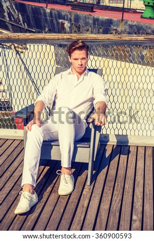American Man traveling in New York. Wearing white shirt, pants, sneakers, wearing, a guy sitting on chair on deck under strong sunshine, relaxing. Boat on background. Instagram filtered effect. - stock photo