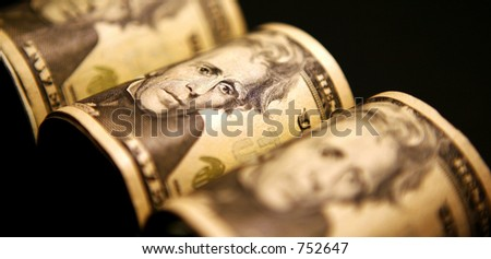 American Money in $20.00 bills rolled up - stock photo