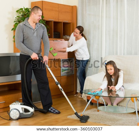 American mother, father and  girl doing general cleaning indoors - stock photo