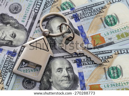 American one hundred dollar notes with house key and keyring. Angled Shot no complete notes shown. - stock photo