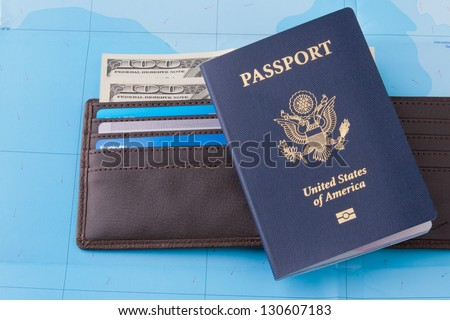 American passport and wallet with dollars cash and credit cards on map background for business travel concept. - stock photo