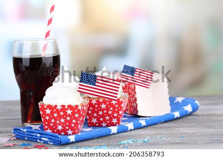 American patriotic holiday cupcakes and glass of cola on wooden table - stock photo