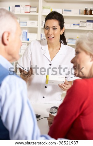 American pharmacist dispensing to senior couple - stock photo
