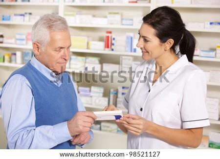 American pharmacist serving  senior man in pharmacy - stock photo