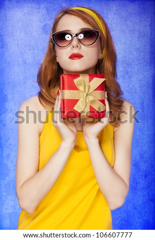 American redhead girl in sunglasses with gift. Photo in 60s style. - stock photo