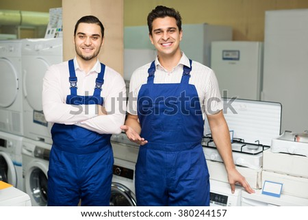 american servicemen in blue uniform smiling at household appliances shop - stock photo