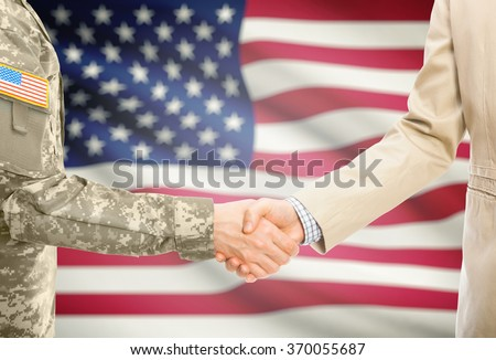 American soldier in uniform and civil man in suit shaking hands with national flag on background - United States - stock photo