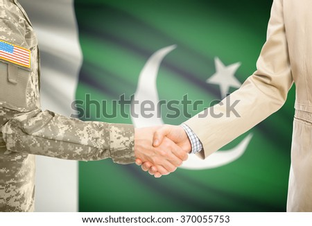 American soldier in uniform and civil man in suit shaking hands with national flag on background - Pakistan - stock photo