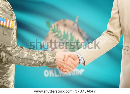 American soldier in uniform and civil man in suit shaking hands with USA state flag on background - Oklahoma - stock photo