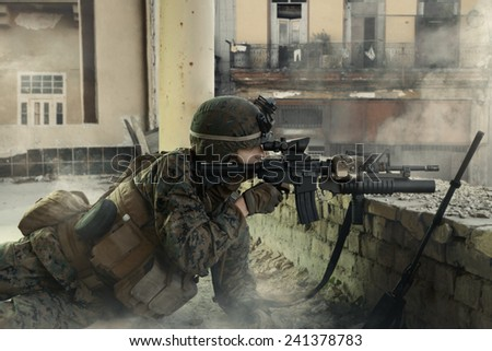 American soldier on the battlefield in an attack/defensive position. Soldier lying in the shelter. - stock photo