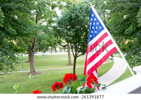 American Stars and Stripes flag flying from a balcony or patio overlooking a park with trees in a patriotic gesture or to celebrate the 4th July and Independence Day - stock photo