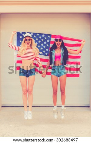 American style. Two cheerful young women holding American flag behind them while jumping against the garage door - stock photo
